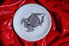 Barwiony bielu talerz z skarabeuszem kłaść na glansowanym czerwonym płótnie Zdjęcia Stock