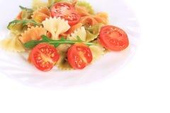 Barwiony farfalle na bielu talerzu z pomidorami Fotografia Royalty Free