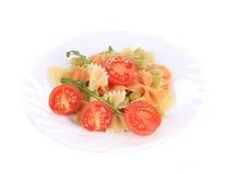 Barwiony farfalle z pomidorami na bielu talerzu Zdjęcie Royalty Free