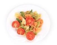 Barwiony farfalle z pomidorami na bielu talerzu Fotografia Stock