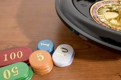 Barwiony kasyno i ruleta szczerbimy się na drewnianym stole fotografia stock