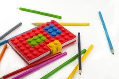 Barwiony notatnik i ołówki na białym tle Fotografia Stock