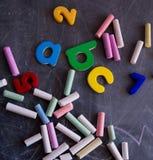 Barwiony pisze kredą liczby i listy na blackboard Zdjęcia Royalty Free