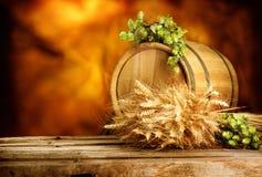 Baryłka piwo z chmiel rożkami pszenicznymi na rocznika drewnianym stole ucho i Zdjęcie Royalty Free