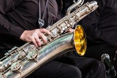 Barytonowy saksofon kłama na kolanie muzyk w czarnej koszula i spodniach Prawa ręka kłama na drewnianym wiatrowym instru fotografia royalty free