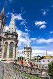 Basílica de nossa senhora do rosário e das bandeiras de países diferentes contra o céu Lourdes, França, Hautes Pyrenees fotografia de stock royalty free