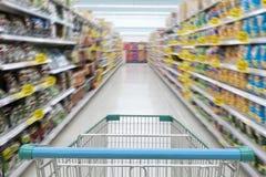 Bas-côté de supermarché avec le caddie bleu vide avec le fond de defocus de client photographie stock