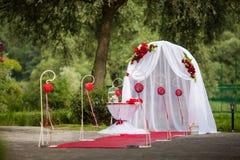 Bas-côté romantique de mariage de valentyne en parc avec les décorations rouges Photo libre de droits