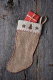 Bas de Noël avec le présent enveloppé par rouge Photos stock