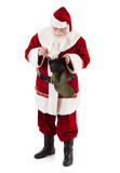 Bas de Santa Claus Putting Gift Into Christmas Images stock