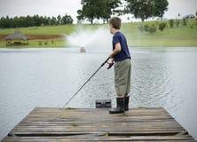 Bas- fiske för pojke på fördämningen eller lakepir Arkivfoto