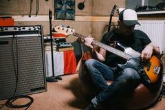 Bas- gitarrist som spelar gitarren i musikstudio Fotografering för Bildbyråer