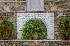 Bas-hulp en bloemen, binnenplaats van de Griekse Orthodoxe Huwelijkskerk in Cana, Israël Royalty-vrije Stock Fotografie