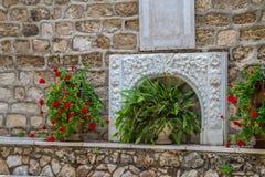 Bas-hulp en bloemen, binnenplaats van de Griekse Orthodoxe Huwelijkskerk in Cana, Israël Stock Afbeelding