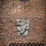 Bas-hulp van monarch in brons op bakstenen muur in Muiderslot-kasteel holland Stock Foto