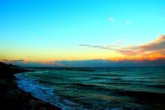 Bas nuages au-dessus de la mer de ondulation pendant le coucher du soleil photo stock