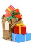 Bas ou sac de Noël complètement avec un bon nombre de présents d'isolement sur le fond blanc Photos stock