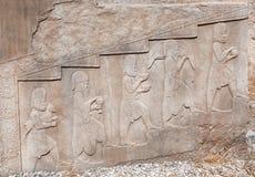 Bas-relevo de pedra com imagens dos povos que trazem o alimento e os animais, como doações, em Persepolis histórico, Irã Foto de Stock Royalty Free