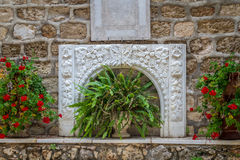 Bas-relevo e flores, pátio da igreja ortodoxo grega do casamento em Cana, Israel fotografia de stock royalty free