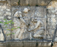 Bas-relief#2. Bas-relief of a woman and a warrior on the stone wall stock images