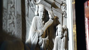 Bas relief art work with morning sun light in Chinese temple. Religious art details stock footage
