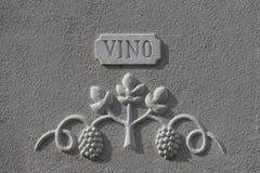 Bas-relief dépeignant des raisins, avec du vin d'inscription Images stock