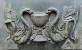bas-relief in the form of two snakes and a bowl on the surface royalty free stock image