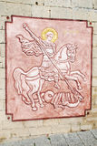 Bas-relief Icon St. George Shoots the Dragon. On the wall Royalty Free Stock Photography