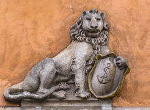 Bas-relief of a lion. With a shield on the wall Royalty Free Stock Photography
