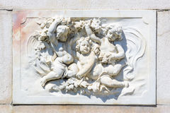 Bas-relief marble sculpture with babies stock photo