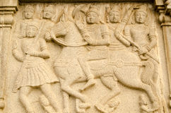 Warrior Buddha on Horseback Frieze. Bas relief sculpture showing the warrior Buddha riding a horse into battle surrounded by soldiers.  Carving on the base of Stock Image