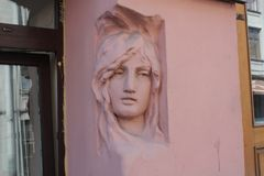 Bas-relief of women`s heads on the facade of the building in Petersburg royalty free stock image