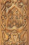 Bas relief in wood - carved wooden door. Wooden background Stock Photos