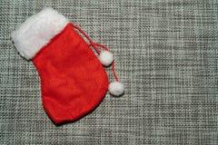 Bas rouge d'ornement de Noël sur un fond gris photographie stock libre de droits