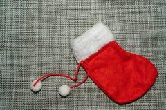 Bas rouge d'ornement de Noël sur un fond gris photo stock