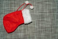 Bas rouge d'ornement de Noël sur un fond gris photographie stock