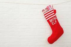 Bas rouge de Noël complètement des cadeaux accrochant sur le mur de briques, l'espace pour le texte image stock