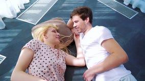 Bas supérieur de jeunes amants dans les rayons du soleil sur le plancher de la pièce vide banque de vidéos