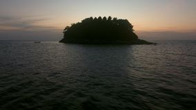 Bas vol au-dessus de bateau de pêche près d'île sauvage avec la vue de coucher du soleil Image stock