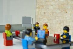 Basa att ge ett samtal till hans lag i hans kontor, fokus på framstickandet arkivbild