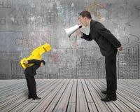 Basa genom att använda megafonen som ropar på anställd som bär guld- dollar s Arkivfoto