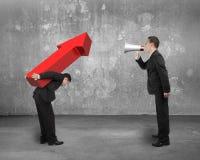 Basa genom att använda megafonen som ropar på anställd som bär röda pilsig Arkivbild