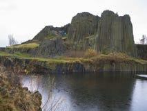 Basalt pillars lava vulcanic rock formation organ shape with lak. E panska skala and group of tourist in blue jacket in kamenicky senov prachen czech republic Royalty Free Stock Images