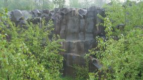 Basalt pillars in the rain. Basalt columns in the pouring rain in nature between the bushes stock video