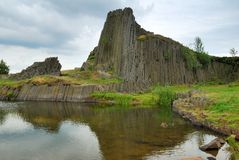 Basalt rock hill and clear pond Stock Images