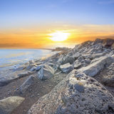 Basalt Rocks Seashore with Black Seashell. Volcanic seashore dawn with wet basalt stones, reflecting the surrounding color and a black seashell in hdr stock photo