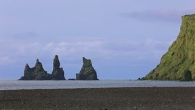 The basalt sea stacks Reynisdrangar. Situated under the mountain Reynisfjall near the village of Vik, southern Iceland stock footage