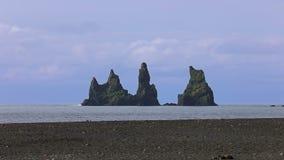 The basalt sea stacks Reynisdrangar. Vik, Iceland. The basalt sea stacks Reynisdrangar situated under the mountain Reynisfjall near the village of Vik in stock footage
