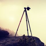 Basalt tripod with professional camera on the peak ready for photography. Sandstone peaks increased from gold foggy background Royalty Free Stock Photography