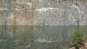 Basalt wall reflected into volcanic lake. UHD 4K stock video footage